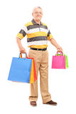 Full length portrait of a mature gentleman with shopping bags Stock Photography