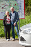 Full-length portrait of mature husband and wife standing behind the map while traveling by car together Royalty Free Stock Images