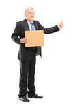 Full length portrait of a mature man in suit hitchhiking Royalty Free Stock Photo