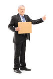 Full length portrait of a mature man in suit hitchhiking Royalty Free Stock Photos
