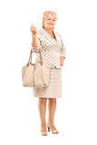 Full length portrait of a mature woman posing with a purse bag Royalty Free Stock Images