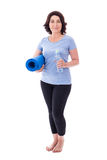 Full length portrait of mature woman in sportswear with yoga mat Stock Images