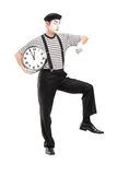Full length portrait of a mime artist holding a clock and checki Stock Photography