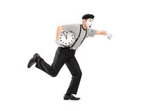 Full length portrait of a mime artist holding a clock and running late royalty free stock photography