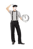 Full length portrait of a mimic holding a clock and thinking Stock Images