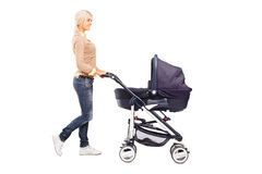 Full length portrait of a mother pushing a baby stroller Stock Images
