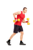 Full length portrait of a muscular athletic man lifting dumbbell Royalty Free Stock Photos