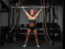 Full length portrait of muscular woman in a gym doing heavy weight exercises Stock Photography