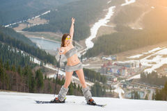 Full length portrait of naked skier. Smiling woman is having fun on snowy slope, wearing sunglasses, boots and skis stock photo