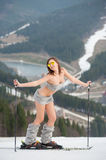Full length portrait of naked skier. Young girl is posing on snowy slope in the mountains, wearing boots and skis. Ski resort, slope and forest on background royalty free stock image