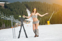 Full length portrait of naked woman skier. Girl is smiling, having fun on snowy slope, wearing sunglasses. Boots and skis. Ski lift and forests on the blured stock image