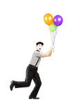 Full Length Portrait Of A Young Mime Artist Holding Balloons Stock Image