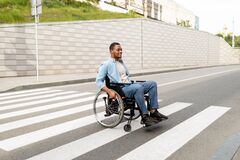 Free Full Length Portrait Of Impaired Young Black Guy In Wheelchair Crossing City Street, Copy Space Royalty Free Stock Photo - 220745155