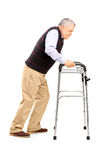 Full length portrait of an old man struggling to move with walker. Isolated on white background stock images