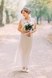 Full length portrait of one beautiful sensual young bride in light white dress and posing at park holding wedding Stock Photos