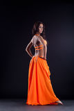Beautiful oriental dancer with long hair. Full length portrait of oriental dancer in orange costume Royalty Free Stock Images
