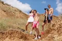 Full-length portrait of pairs of fellows and girls holding hands on a top of a valley on a blurred natural background. Full-length portrait of smiling girls and Royalty Free Stock Image