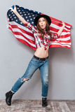 Full length portrait of a patriotic girl holding USA flag. Full length portrait of a patriotic cheerful girl holding USA flag and looking at camera isolated over Royalty Free Stock Photography