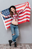 Full length portrait of a patriotic girl holding USA flag. Full length portrait of a patriotic young girl holding USA flag isolated over gray background Stock Photo