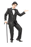 Full length portrait of a performer in black suit gesturing with. A cane isolated on white background Royalty Free Stock Photo