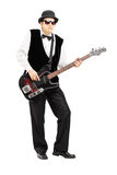 Full length portrait of a person playing a bass guitar. Isolated on white background Stock Image