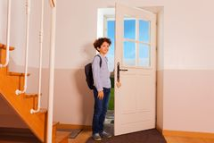 Preteen boy coming back home from school. Full-length portrait of preteen curly boy standing at hallway, getting ready to go out or coming back home from school Royalty Free Stock Images