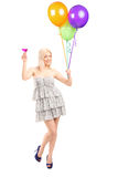 Full length portrait of a pretty blond female holding balloons a Royalty Free Stock Image