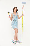 Full length portrait of pretty girl, holding hammer and painting. Full length portrait of pretty girl, in gray shirt and denim overall, holding hammer and Royalty Free Stock Photos