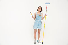 Full length portrait pretty girl, holding hammer and painting ro. Full length portrait pretty girl, in gray shirt and denim overall, holding hammer and painting Stock Images