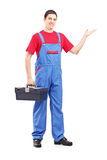 Full length portrait of a repairman holding a tool box. And gesturing on white background royalty free stock image