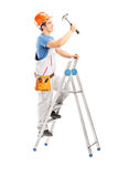 Full length portrait of a repairman on a ladder working with a h Royalty Free Stock Photography