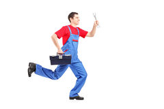 Full length portrait of a repairman running with a wrench Stock Photo