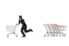 Full length portrait of a robber stealing an empty pushcart Stock Images