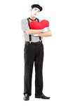 Full length portrait of a sad mime artist holding a red heart Royalty Free Stock Images