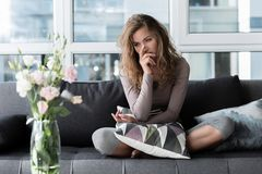 Sorrowful lady sitting on cozy sofa. Full length portrait of sad woman locating on comfortable couch. She looking at flowers in apartment. Affliction concept Royalty Free Stock Photography