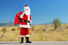 Full length portrait of a Santa claus with bag full of presents. Standing on a road and posing Royalty Free Stock Images