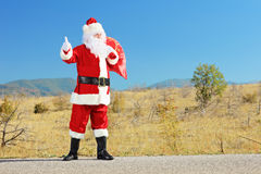 Full length portrait of a santa claus with bag hitchiking on an Stock Photos