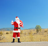 Full length portrait of a santa claus with bag on an open road h. Itchiking, shot with a tilt and shift lens Stock Photos