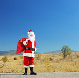 Full length portrait of a Santa claus with bag standing on road Royalty Free Stock Image