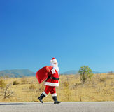 Full length portrait of a santa claus with bag walking on an ope Royalty Free Stock Photography