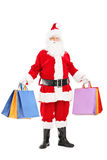 Full length portrait of a Santa Claus holding shopping bags. Isolated on white background Stock Photos