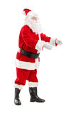 Full length portrait of a Santa Claus about to take something Stock Photos