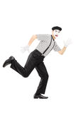 Full length portrait of a scared male mime artist running away Stock Images
