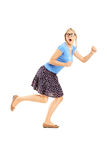 Full length portrait of a scared woman running away Royalty Free Stock Photos
