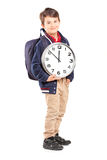 Full length portrait of a school boy with backpack holding a clo Royalty Free Stock Photography