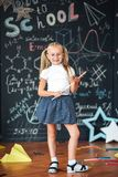 Full-length portrait schoolgirl with glasses and ruler looking like a strict teacher raised her pointer to draw attention against royalty free stock photography