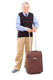 Full length portrait of a senior gentleman standing with a trave Royalty Free Stock Image