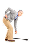 Full length portrait of a senior man with back pain trying to pi. Ck up a cane  on white background Royalty Free Stock Images