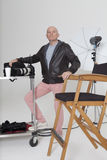 Full length portrait of senior photographer with equipments in studio royalty free stock photo