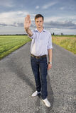 Full length portrait of senior young man showing stop gesture on country road Stock Image